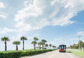 Trolley fährt am Palmenstrand entlang auf Anna-Maria-Island.
