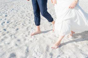 Brautpaar barfuß im Strandsand.