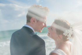verliebtes Brautpaar, zart verdeckt vom Schleier der Braut.
