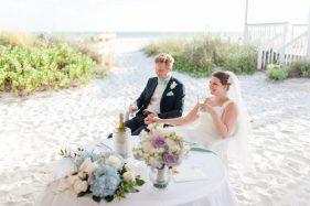 Brautpaar sitzt am Meer am Tisch und trinkt Champagner