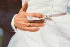 Hand das Bräutigams an der Taille der Braut.