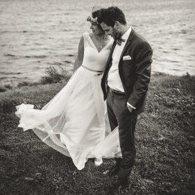 Brautpaar steht an der Küste.