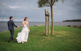 Brautpaar geht Hand in Hand am Ufer auf Rügen