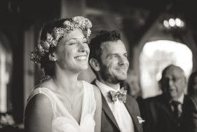 Lachende Braut bei der Trauung, Bräutigam unscharf im Hintergrund.