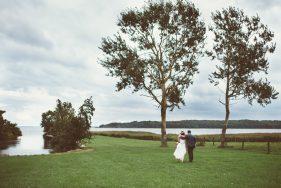 Braut und Bräutigam gehen Hand in Hand über eine Wiese. Mit dem Rücken zur Kamera.