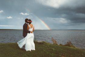 Brautpaar steht an der Küste und betrachtet einen Regenbogen.