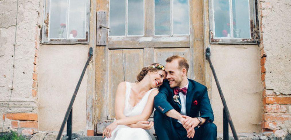 verliebtes Brautpaar sitzt auf einer Steintreppe.
