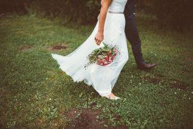 Brautpaar geht über Rasen mit dem Brautstrauß in der einen Hand.