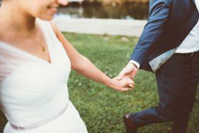 Braut und Bräutigam gehen Hand in Hand über eine Wiese.