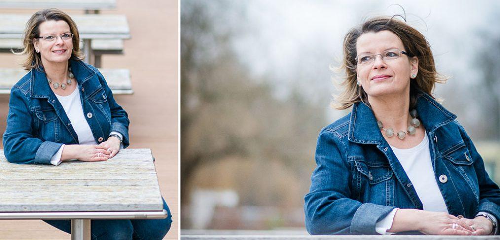 Geschäftsfrau sitzt an einem Holztisch im Freien, Businessfoto.