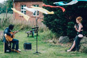 Gitarrist und Frau auf einer Wiese am Kulturgut Wrechen
