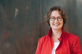 lächelnde Geschäftsfrau vor rostfarbenem Hintergrund